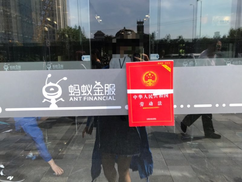 Photo of a booklet of China's labor laws taped onto the glassdoor of Ant Financial